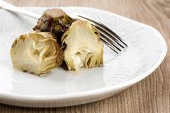 Carciofi in piatti o ciotola con la forcella immagine stock