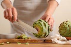 Carciofo su un fondo leggero, concetto dei tagli del cuoco unico che cucina alimento saporito e sano, menu, libro di ricetta, dis fotografia stock