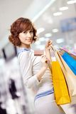 Card. Curly young woman in shop with a credit card Royalty Free Stock Photography