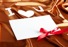 Card with. I love you on gold silk background and red ribbon Royalty Free Stock Photos