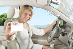 Card. Portrait of young beautiful woman sitting in the car royalty free stock photography