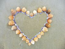 Card background shells on the beach top view heart shape next to the ocean