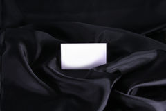 Card on Black. A blank white business card on black satin. The blank card is copyspace for you text in an elegant setting. Can be used as a business card, thank Royalty Free Stock Image
