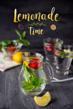 Card with bright phrase Lemonade time and Flavored water with fresh strawberries and mint in glass jars on a black wooden table wi stock photography