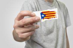 Card with Catalonia flag in hand. Selective focus Royalty Free Stock Photos