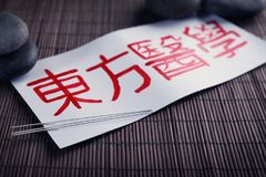 Card with chinese word and acupuncture needles. On table royalty free stock images
