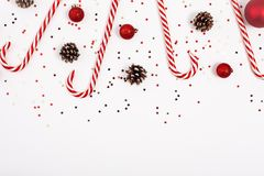 Christmas border made with candy cane, red balls and cones on white background. View from the top royalty free stock photography