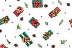 Christmas pattern with gifts, cones, fir tree branches and winter berries on white background. Flat lay royalty free stock image