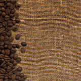 Card with coffee beans on background sacking. 