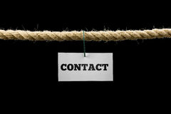 Card with Contact text hanging by wire from a rope isolated on b Royalty Free Stock Image