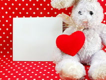 Card and cute rabbit doll with red heart on red polka dot Stock Photography