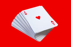 Card deck. A deck of cards with the Ace on top, isolated on red background Stock Photos