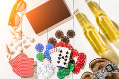Card deck surrounded by poker chips and scattered seashells on white wooden background with copy space Royalty Free Stock Photos