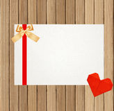 Card decorated with bow and red heart on wooden background Stock Photography
