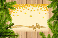 Card decorated with golden bow and stars on wooden background Stock Photography