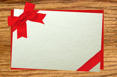 The card decorated with a red bow on envelope over wooden backgr Royalty Free Stock Photos
