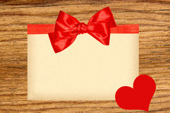 Card decorated with red ribbon, bow and heart on wooden Stock Photography