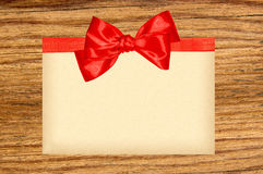 Card decorated with red ribbon and bow on wooden Stock Image