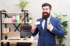 Card design. Guy formal suit stand in office. Businessman hold blank card. Useful contacts. Bearded hipster top manager. Show card. Banking services. Private stock images