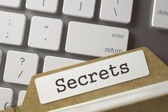 Card File with Inscription Secrets. 3D. Folder Index with Inscription Secrets on Background of White Modern Keypad. Business Concept. Closeup View. Blurred Stock Photo