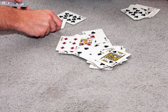 Card Game. A game of cards being played on some blue carpet. Some of the cards are face up in a pile and a persons hand is in view Stock Photo