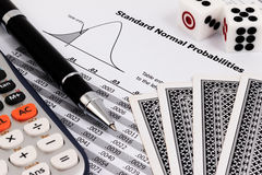 Card game, calculator, dice and pen on standard normal probabilities table. Royalty Free Stock Photo