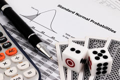 Card game, calculator, dice and pen on standard normal probabilities table. Royalty Free Stock Photos