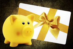 Card gift with piggy bank, golden ribbon bow, Isolated on brown Royalty Free Stock Images