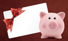 Card gift with piggy bank, red ribbon bow,  on red Stock Image