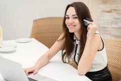 card grund shopping för dof-fokushanden online mycket Ungt och nätt flickasammanträde på en bärbar dator och ett M Royaltyfri Foto