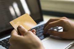 Card  in hand and entering security code using laptop keyboard. Stock Image