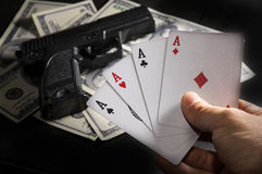Card in hand with gun and money for background. Royalty Free Stock Photo