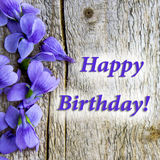 Card `Happy birthday`, light wooden background, violet flowers of violets Royalty Free Stock Image