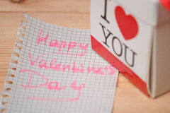 Card with Happy Valentines day and box on wooden background Stock Photography