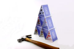 Card House and Claw Hammer. A house or pyramid made from playing cards and a claw hammer royalty free stock photography