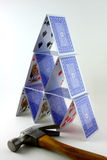 Tower of cards with hammer. Tower of balancing playing cards in pyramid shape with hammer in foreground, business concept stock photos