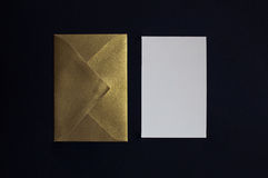 Card inbjudan och det guld- kuvertet på den svarta bakgrunden Arkivfoton