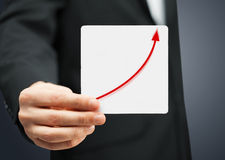 Card with increasing graph on it. Man in suit holding card with increasing graph on it Royalty Free Stock Photos