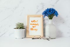 Card with inspiration quote. Collect moments not things in a wooden photo frame in front of pale marble pastel background Royalty Free Stock Photography