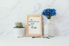 Card with inspiration quote. Do small things with great love in a wooden photo frame in front of pale marble pastel background Stock Photos
