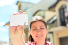 Card with a key in hand of happy woman Stock Photography