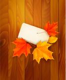 Card with leaves on wooden background. Stock Photo