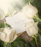 Card with Love Letter and White Roses on the Wooden Table Royalty Free Stock Image