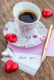Card with Message Love You, cup of coffee and chocolate candy Royalty Free Stock Image