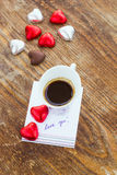 Card with Message Love You, cup of coffee and chocolate candy Stock Photos