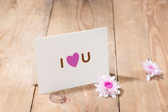 Card with Message Love You on the Letter on wooden background Stock Images