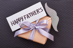 Card and mustache on gift. Present box on black surface. Stylish congratulation for dad Stock Photos