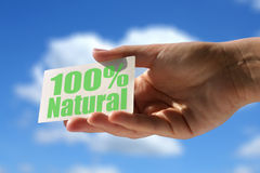 Card with 100% natural inscription. Hand holding business card with 100% natural inscription Stock Images