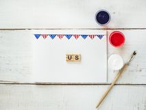 Card with a pattern of the US Flag. Word US and colored gouache paints on a white, vintage, wooden table. Top view, close-up. Concept of an independent, strong Royalty Free Stock Photo