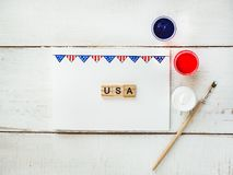 Card with a pattern of the US Flag. Word USA and colored gouache paints on a white, vintage, wooden table. Top view, close-up. Concept of an independent Stock Images